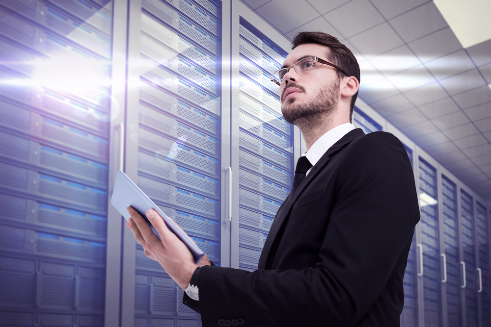 Businessman looking away while using tablet against server room