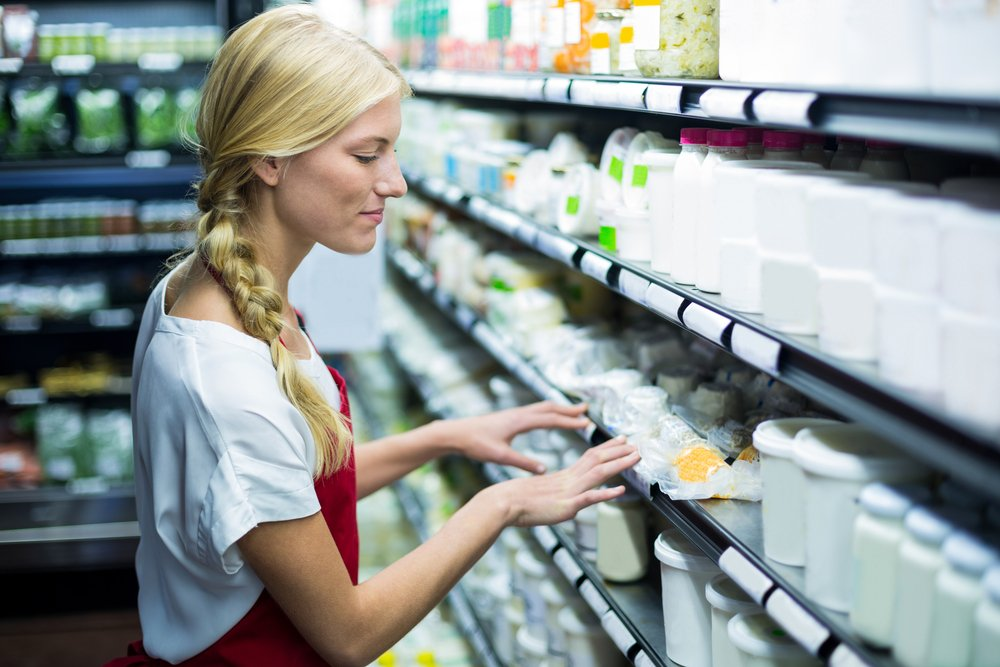 Female staff checking grocery products in shelf of supermarket