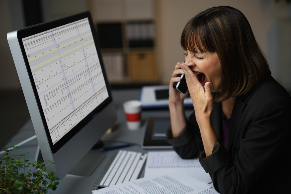 Tired Businessman at her Desk, Showing Yawning Gesture While Talking to Someone on Mobile Phone.